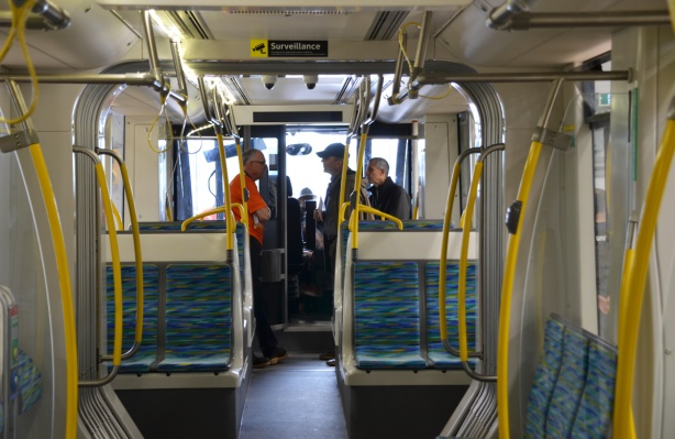 a few people talking at the front of new Crosstown train, from farther back in the train.