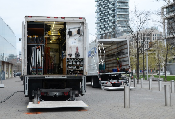the back of two large trucks with their doors open as cables, tools and other equipment for filming is being load back into the trucks