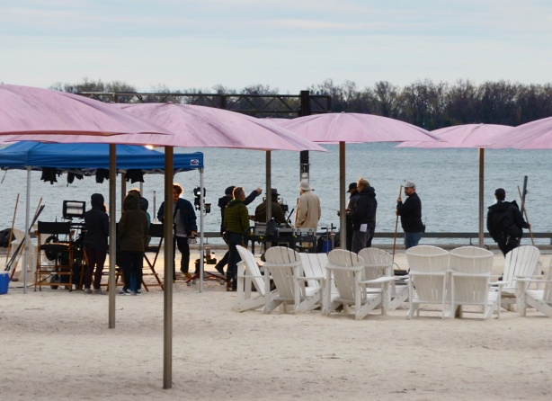 a group of people standing near the waterfront at sugar beach with its pink umbrellas and white muskoka chairs