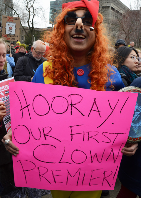 a man in an orange wig and clown costume holds a sign on pink bristol board that says Hooray! Our first clown premier