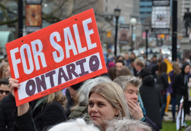 at a Queens Park demonstration on May day, a woman holds a red and white for sale sign with the word Ontario written in the blank, for sale Ontario