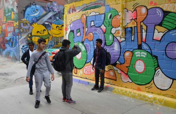 one boy is filming another as he talks in the alley, in front of a colourful mural