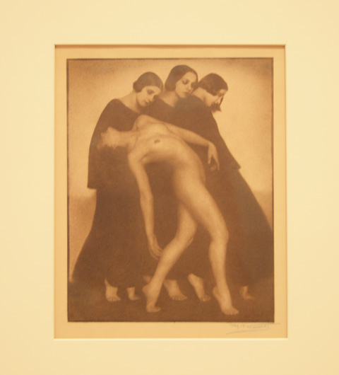 vintage sepia toned photo of four women moving together, 3 are dressed in long plain dresses and they are close together and supporting a naked woman who has her back arched while she walks (with her head looking backwards)