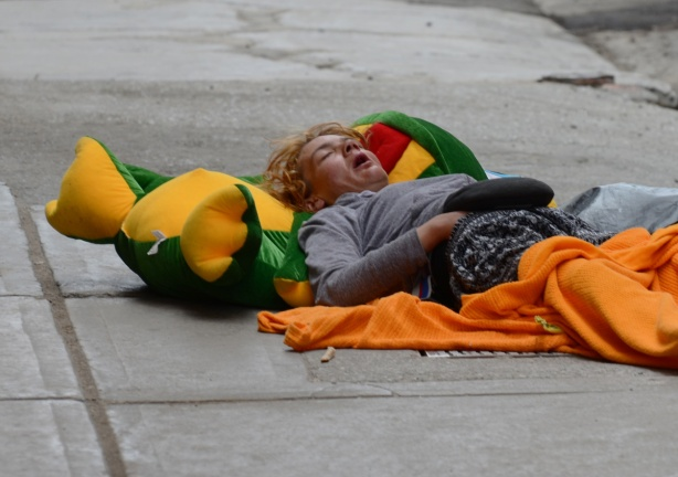 a person is sleeping on their back on the sidewalk. Their head is on a large green frog pillow