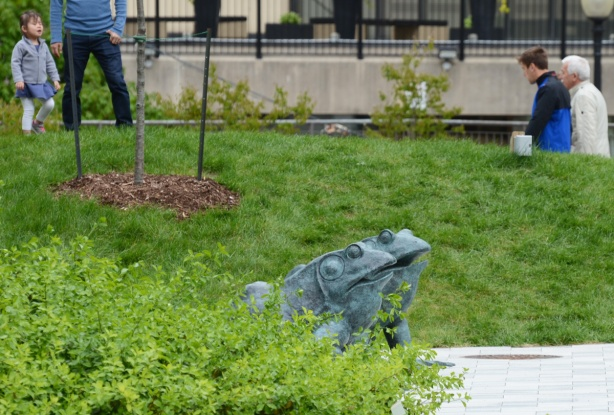 two bronze sculptures of frogs in a park
