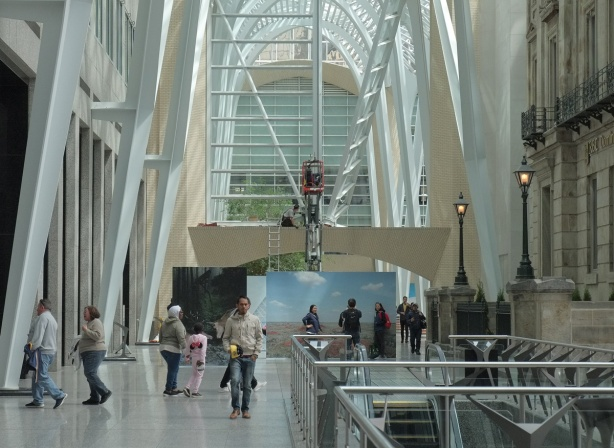 people in Allan Lambert Galleria, a couple of large photos, a workman on a crane,