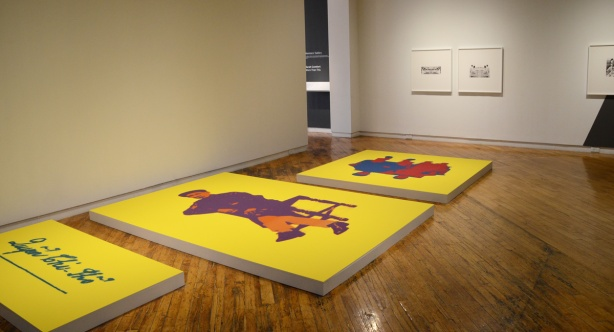 art gallery room with three large canvases on the floor, all wth bright yellow backgrounds