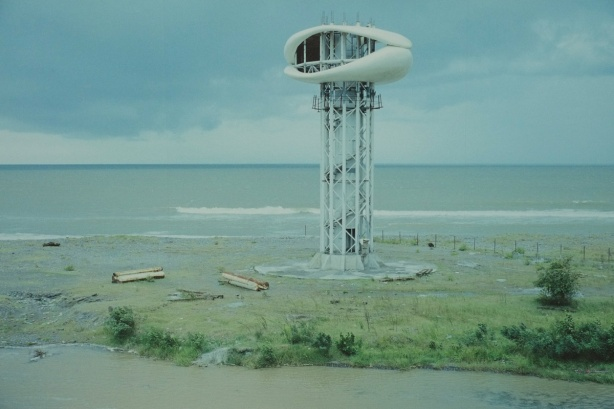 large photo of a oval shaped structure on the top of a tower, on the coast, surrounded by barren land, abandoned building, in Anaklia Georgia (former USSR republic)