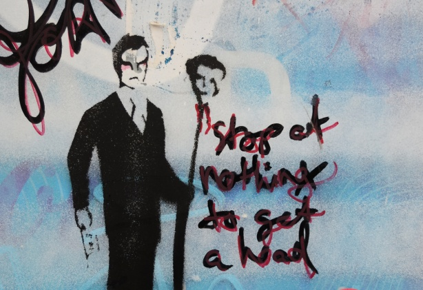 stencil on a wall that has been spray painted a pale blue, black ink, man holding a tall stick on the top of which is a head, words that say, stop at nothing to get a head