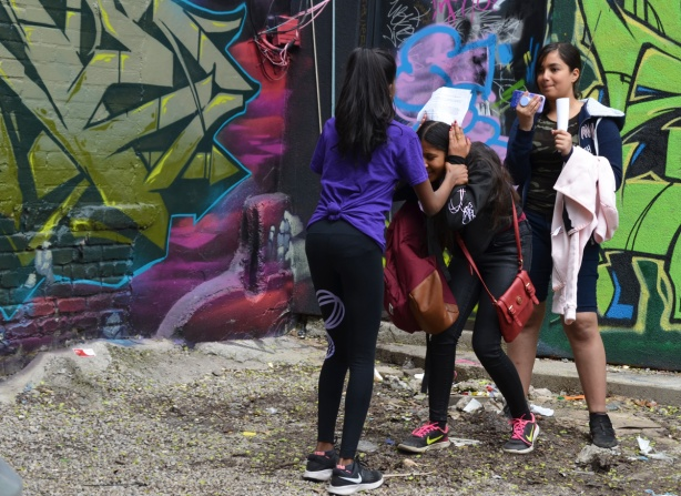 three girls working on a video in a corner of an alley, on is filming with a phone and one is talking and one is holding the paper with the words on it.