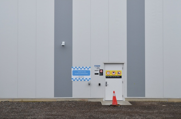 exterior of new crosstown maintenance facility with double grey stripes, a doorway with many warning signs.
