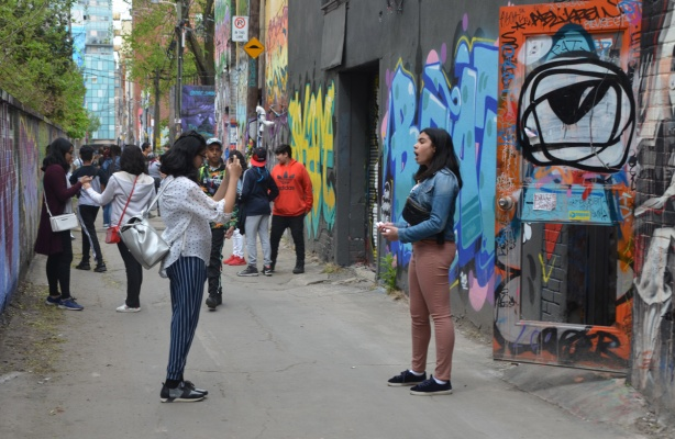 one woman is filming another woman who is talking in graffiti alley in main part of alley