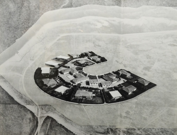 an aerial photo of a U shaped street of suburban houses, surroundings are blacnked out with translucent paper or something similar