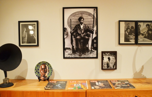 a collection of pictures on the wall and Life magazines on a table, part of Heave, an exhibit by Carrie Mae Weems at University of Toronto art museum and gallery