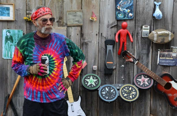 a man in tie dyed shirt and red bandana, and holding a can of beer, stands in front of a wall with many objects attached to it.