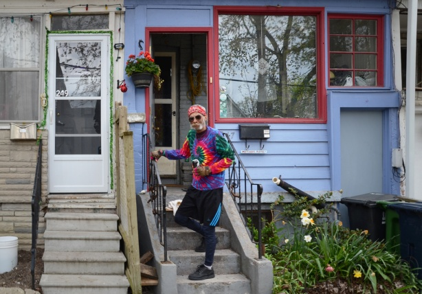Johnny in a tie dyed shirt standing on the front steps of a blue house with red trim