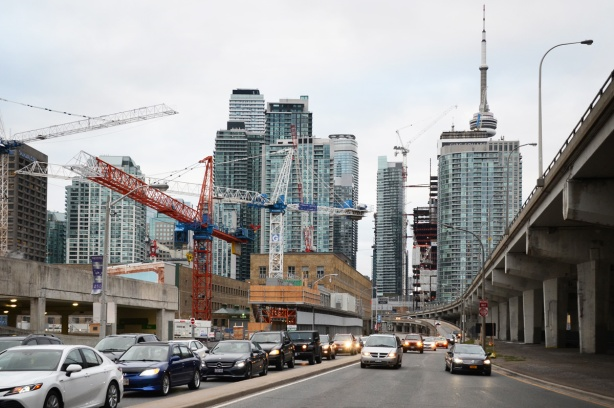 downtown Toronto, looking west towards all the tall buildings, looking along the Lakeshore with lots of traffic on it, many buildings in the foreground under construction with 7 cranes in the photo