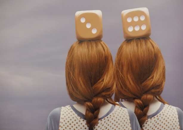 close up of a Patty Maher photograph, Parallel Universe, the back of two red headed women, both with large dice on their head, one die per head,