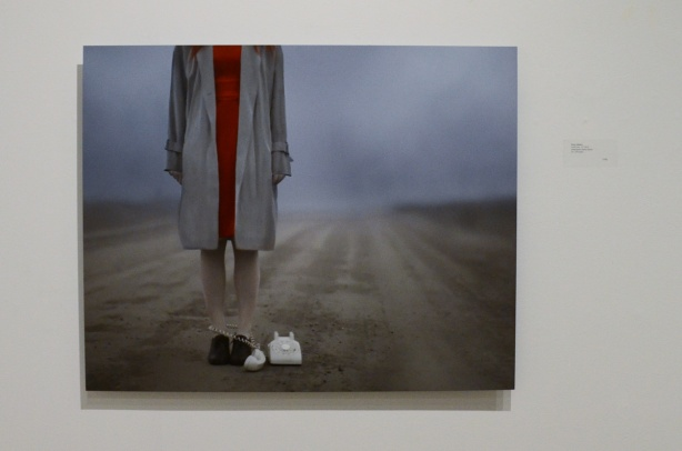 A Patty Maher photo of a woman standing on a deserted country road with an old rotary phone at her feet, her head has been cropped out of the photo, foggy in the background