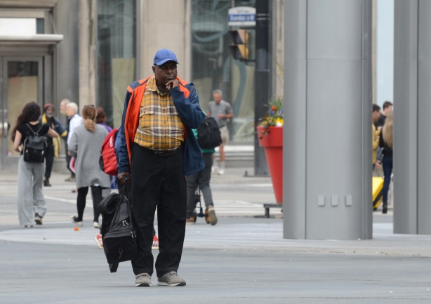 a man stands in dundas square, with a rolling suitcase in one hand