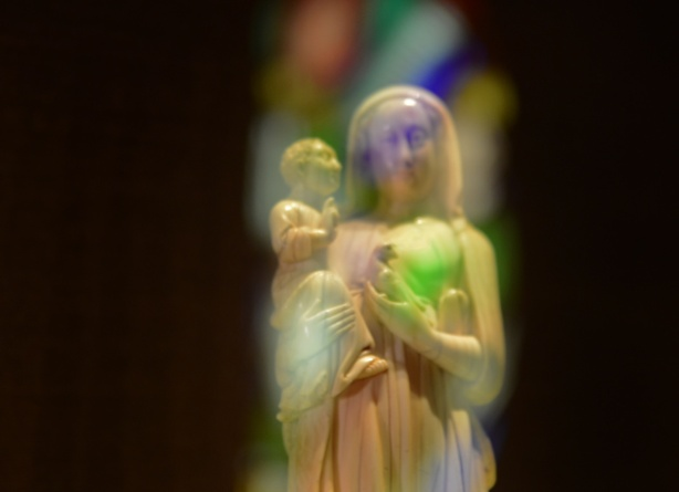 a small white statue of Mary holding the baby Jesus, lit by light coming through a stained glass window behind it