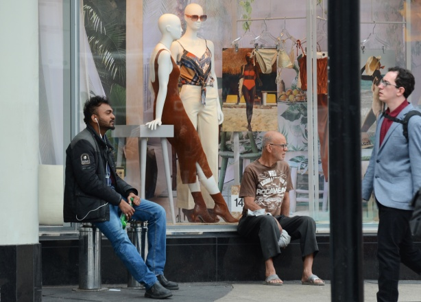 two men sit beside a store window with female mannequins in summer clothes, another man is walking past