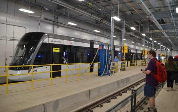 inside the new maintance building, a new grey, black and white crosstown train on display, people walking past it and taking pictures