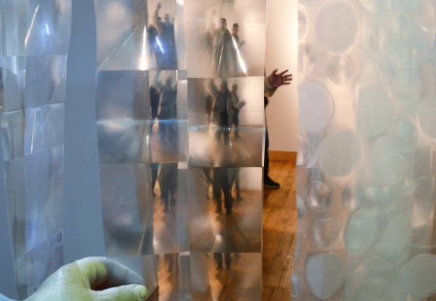 art installation that uses strips of plastic shower curtain. The squares in the plastic make the person on the other side appear many times - one each in every square