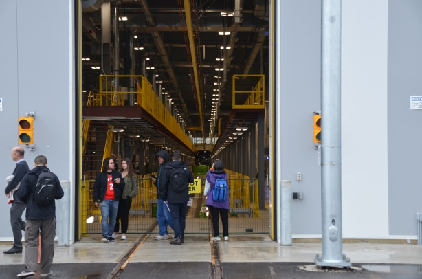 people standing outside the open door of the crosstown facility, can look inside
