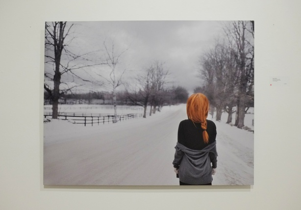 a large photo of a red headed woman, long hair, in a braid, standing on a snow covered road with her back to the camera, in the countryside