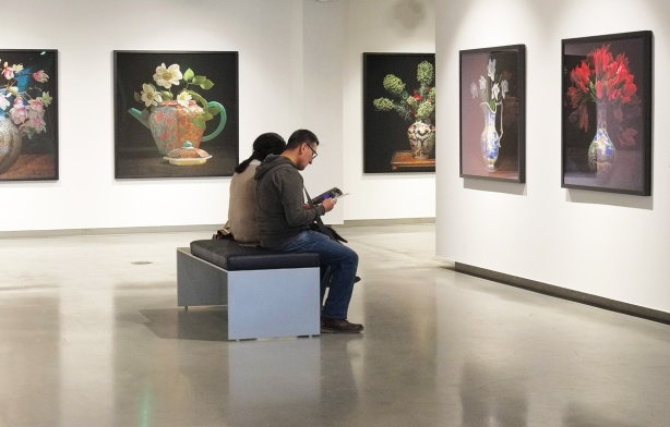 people sitting on a bench in a gallery, reading, large photos of flower bouquets on the walls around them