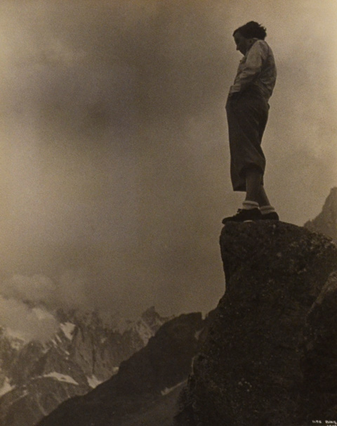 anold photo by Ilse Bing of a woman standing on a rock high upon a mountian. She's looking down over the valley below