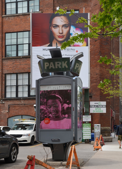 a pink and black photo of a girl's head, on a small display in a parking lot, with a Huawei ad behind it. Ad features that head of a model