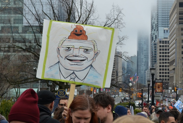 a person holds up a sign that is a drawing of Doug Ford's head with a poop emoji on top of his head