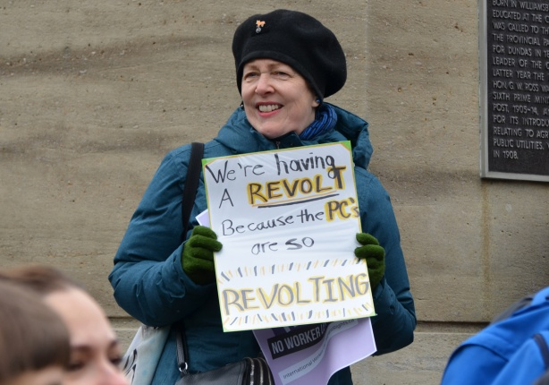 a woman in a blue coat and black beret holds a sign that says We're having a revolt because the PC's are so revolting