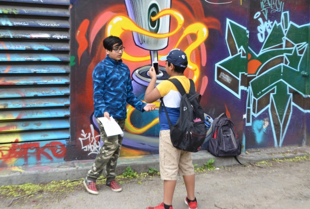 a boy in shorts and a baseball cap is filming another boy in blue fleece and camo pants as he is talking in front of a mural in graffiti alley