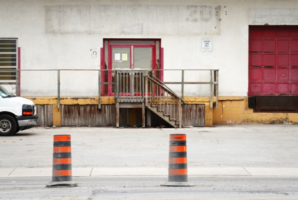 two orange and black traffic contruction cones on the street in front of an old white industrial building with red door frames and a wood loading dock with yellow trim