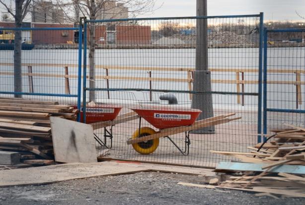 orange wheel barrows at a construction site beside a lake