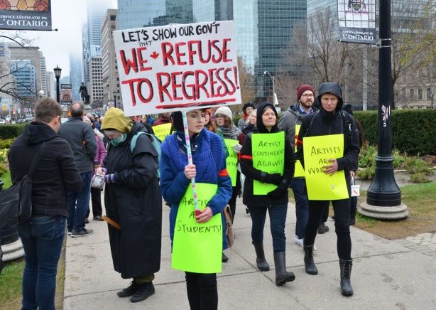 a group of artists with bright yellow and light green signs walks as a group towards a protest in front of Queens Park, the woman at the front also has a sign on a stick that says We refuse to regress