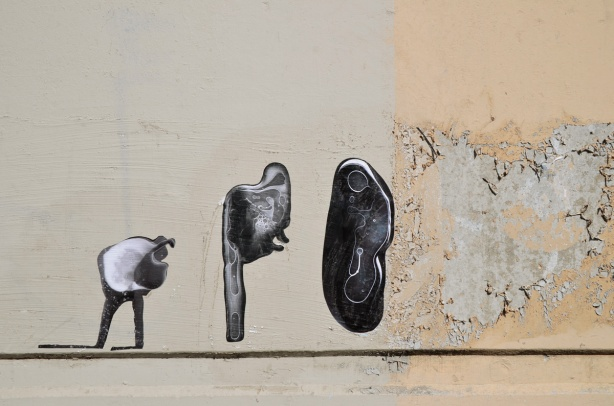 three black and white photo paste ups that look like ameobas or primitive life forms on a concrete wall, outdoors,