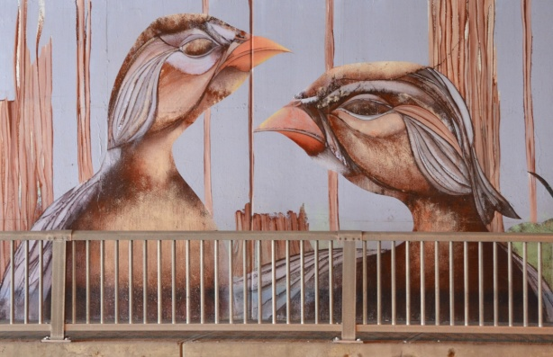part of a mural, two bird heads in orange and brown tones