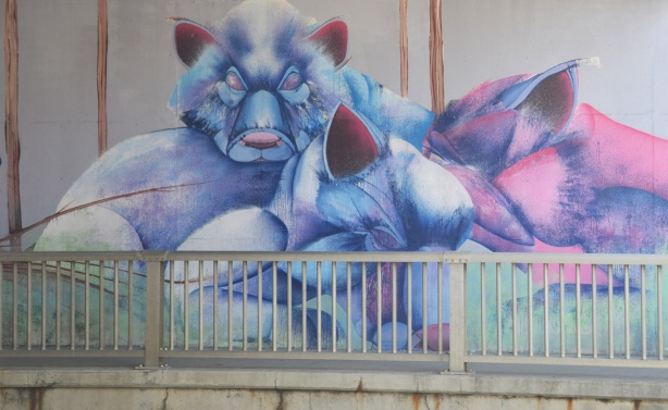 part of a mural by Christopher Ross on an underpass wall in pinks and blues, a large blue bear