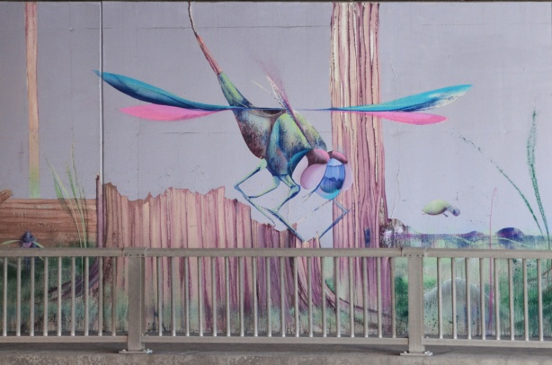 part of a mural by Christopher Ross on an underpass wall in pinks and blues, a dragonfly