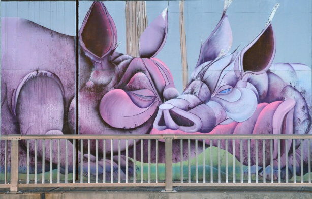 mural on a wall, two fat pink pigs snout to snout
