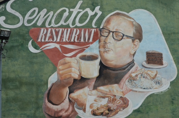 large mural on the side of the Senator restaurant, a man in glasses holds a steaming cup of coffee with plates of food in front of him, by his shoulder, bacon and eggs with toast as well as a plate with a sandwich and a side of salad. A third plate has a piece of chocolate cake