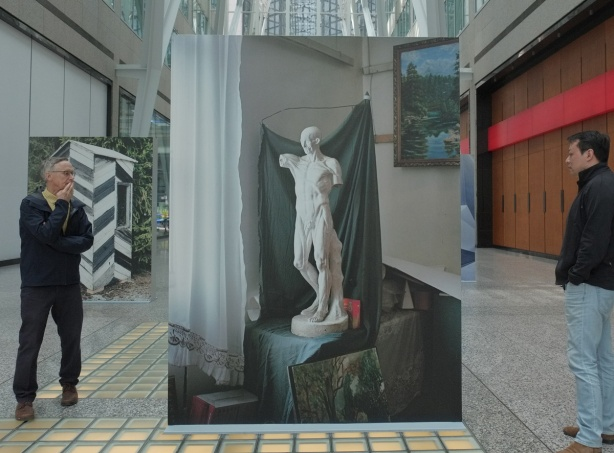 large picture of an old white statue, Brookfield Place, 2 men looking at it. Photo's title is A sculptural model in a student atelier, Spitak Armenia
