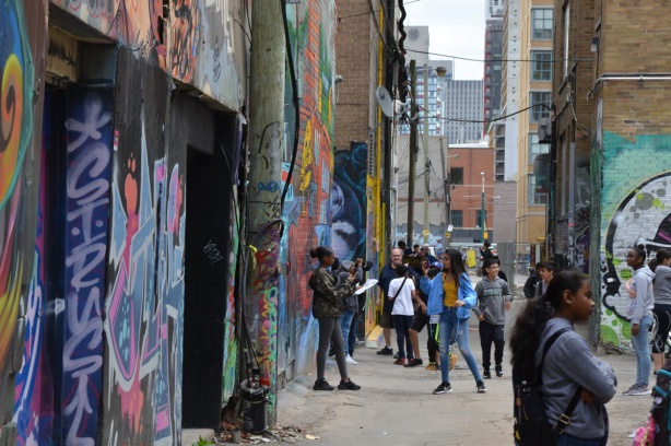 teacher, students, and other people in graffiti alley