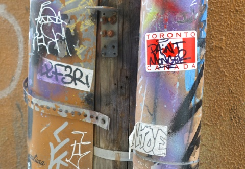 a red and white Canadian flag printed on a sticker that says Toronto Canada that someone has added their tag to, stuck on a utility pole in an alley