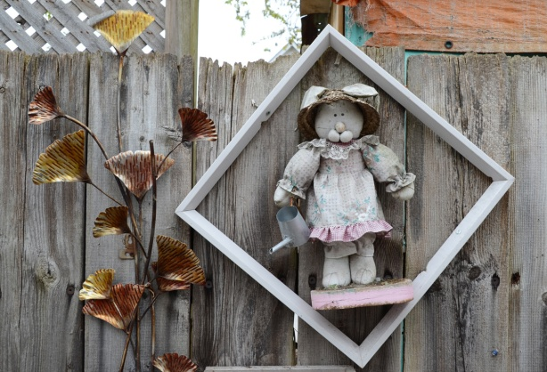 metal leaf art piece attached to a wood fence, stuffed bunny that is faded and grey also attached to the fence