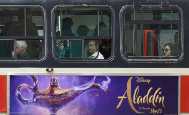 a man and a young girl look out the window of a TTC streetcar with a poster on the side advertising Aladdin movie